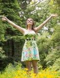 La femme avec des bras a tendu dans le domaine contre des arbres Photos stock