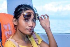 La femme avec des lunettes de soleil s'asseyent sur un bateau Photo stock