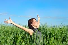La femme avec des mains a augmenté vers le haut dans le domaine de blé Image libre de droits