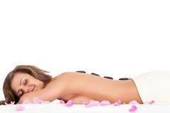 La femme avec des pierres de station thermale desserrent en fonction Photo stock