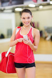 La femme avec des sports mettent en sac, smartphone et écouteurs Photographie stock