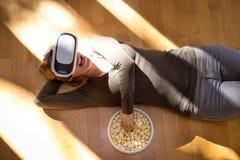 La femme avec des verres de vr mange du maïs éclaté Photos stock