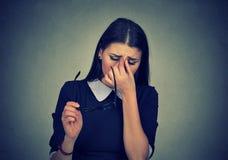 La femme avec des verres frottant ses yeux se sent fatiguée photos stock