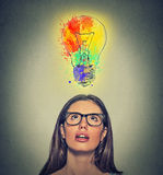 La femme avec des verres a l'idée colorée brillante regardant l'ampoule photographie stock libre de droits