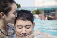 La femme avec des yeux a fermé embrasser l'homme sur la joue dans l'eau dans la piscine Image stock