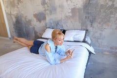 La femme avec du charme se tient dans des mains et utilise le smartphone, se trouve sur grand Photos stock