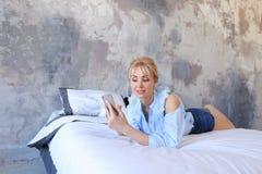 La femme avec du charme se tient dans des mains et utilise le smartphone, se trouve sur grand Image stock