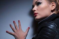 La femme avec gentil composent et les ongles rouges manicure, poussant le wal images libres de droits