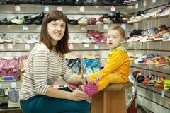 La femme avec l'enfant choisit des chaussures de chéri Photo stock