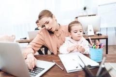 La femme avec l'enfant est venue pour travailler photo libre de droits