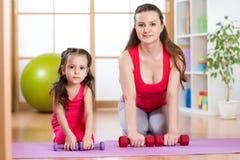 La femme avec l'enfant faisant le gymnase et la forme physique s'exerce photographie stock libre de droits