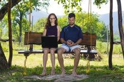 La femme avec l'ordinateur portable et l'homme avec le mobile s'asseyent sur un commutateur en bois Photographie stock