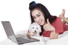 La femme avec l'ordinateur portable et les expositions canines APPROUVENT le signe Image stock