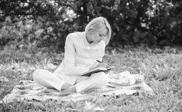 La femme avec l'ordinateur portable ou le carnet s'asseyent sur le pr? d'herbe de vert de couverture Concept de pique-nique d'aff images stock