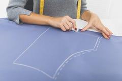 La femme avec la bande de mesure dessine un modèle Photographie stock