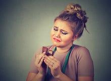 La femme avec la bande de mesure a fatigué des restrictions de régime implorant le chocolat de bonbons Photographie stock