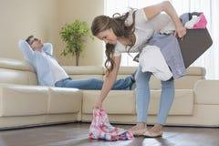 La femme avec la cueillette de panier de blanchisserie vêtx tandis qu'homme détendant sur le sofa à l'arrière-plan photos libres de droits