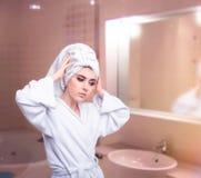La femme avec la serviette sur principal prennent soin de ses cheveux image libre de droits