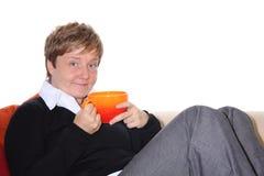 La femme avec la tasse de thé détend sur un sofa Photos stock