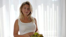 La femme avec le bébé dans le ventre tient des fruits dans le plat et mange des raisins près de la fenêtre, consommation saine clips vidéos