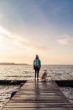 La femme avec le chien apprécient le lever de soleil au lac, randonneur Image libre de droits