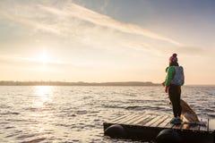 La femme avec le chien apprécient le lever de soleil au lac, randonneur Photographie stock
