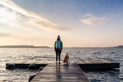La femme avec le chien apprécient le lever de soleil au lac, randonneur Photos stock