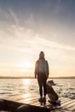 La femme avec le chien apprécient le lever de soleil au lac, silhouette de randonneur Photographie stock