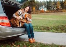 La femme avec le chien s'asseyent ensemble dans le camion de chat et chauffent le thé chaud Image libre de droits