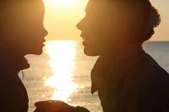 La femme avec le garçon s'asseyent à terre vis-à-vis du soleil Photographie stock libre de droits