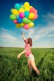 La femme avec le jouet monte en ballon au printemps le champ Photo stock