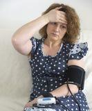 La femme avec le mal de tête mesure la tension artérielle Images libres de droits