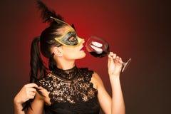 La femme avec le masque de Venise et un verre de vin pour le carnaval font la fête Photos stock