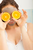 La femme avec le masque facial de boue tient la tranche orange Photographie stock libre de droits