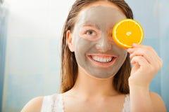 La femme avec le masque facial de boue tient la tranche orange Images stock
