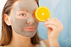 La femme avec le masque facial de boue tient la tranche orange Image libre de droits