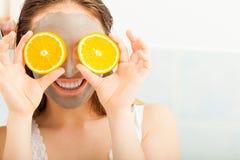 La femme avec le masque facial de boue tient la tranche orange Photos libres de droits