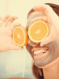 La femme avec le masque facial de boue tient la tranche orange Images libres de droits