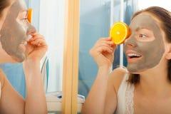 La femme avec le masque facial de boue tient la tranche orange Photos stock