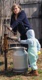 La femme avec le petit fils prend l'eau (2) photographie stock