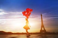 La femme avec le rouge monte en ballon près de Tour Eiffel à Paris Images libres de droits