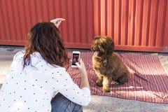 La femme avec le téléphone intelligent mobile prenant une photo de l'eau espagnole font Photographie stock libre de droits