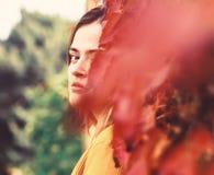 La femme avec le visage caché sur le lierre d'automne laisse le fond photo libre de droits