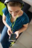La femme avec les écouteurs verts écoute musique de Podcast au téléphone Photos stock