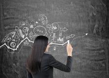 La femme avec les cheveux noirs dessine des icônes d'affaires Image stock