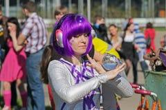 La femme avec les cheveux pourpres montre un tour avec une boule en verre dans VDNH à Moscou Image libre de droits