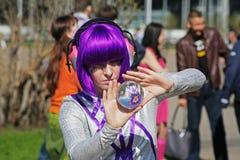 La femme avec les cheveux pourpres montre un tour avec une boule en verre dans VDNH à Moscou Image stock