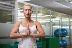La femme avec les mains et les yeux jointifs s'est fermée au studio de forme physique Photographie stock