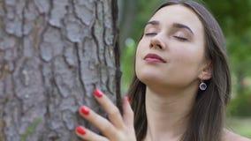 La femme avec les yeux fermés sent l'arbre et l'unité avec la nature, amour de la vie, joie clips vidéos