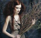 La femme avec lumineux composent avec les branches sèches Photo libre de droits